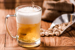 Beer pouring from top in bottle on wood table Royalty Free Stock Image