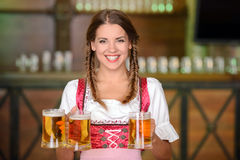 Beer Pub. Beautiful, sexy waiter woman holding glasses of beer in a beer pub Stock Photos