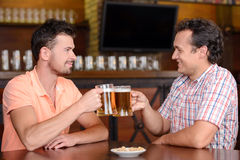 Beer Pub. Friends in beer pub. Two cheerful friends drinking beer and talking at bar Stock Image