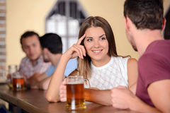 Beer Pub. Beer lovers. Young cheerful couple drinking beer at the bar Royalty Free Stock Photo