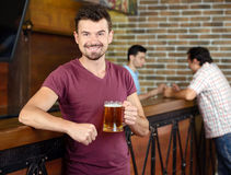 Beer Pub. Man in bar. Handsome young men drinking beer in bar and smiling Stock Photography