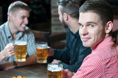 Beer Pub. Meeting at the pub. Three happy friends drinking beer at the pub Royalty Free Stock Images