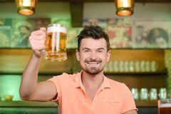 Beer Pub. Night in bar. Portrait of cheerful man drinking beer at the bar Royalty Free Stock Photos