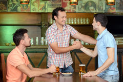 Beer Pub. Old friends meeting. Three cheerful friends meet each other in beer pub Royalty Free Stock Images