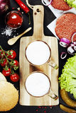 Beer and Raw Ground beef meat Burger steak cutlets with seasonin Royalty Free Stock Images