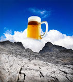 Beer refreshment summer. Beer refreshment in summer, beer mug on white cloud of blue sky in dry mountains royalty free stock images