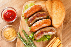 Beer and roast beef or chicken sausage. October fest traditional menu, beer and roast beef or chicken sausage  with ketchup, mustard and rosemary. Wooden cutting Royalty Free Stock Image