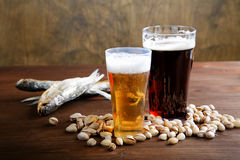 Beer with salty nutlets and  fish Royalty Free Stock Images
