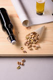 Beer with salty pistachio nuts and a newspaper on wooden table. Royalty Free Stock Photo