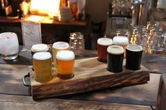 Beer Samples in a Wood Themed Room. Eight beer samples in a burned wood holder on a burned wood table in a warm room royalty free stock photos