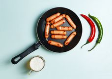 Beer and sausages fried in a frying pan, a top view, blue background. Royalty Free Stock Images