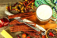 Beer and sausages on an old wooden table. Sale of beer and sausage. Food for beer. Unhealthy food royalty free stock photo