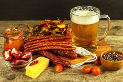 Beer and sausages on an old wooden table. Sale of beer and sausage. Food for beer. Unhealthy food royalty free stock image