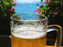 Beer and sea. Glass of cold beer close up, blue sea Stock Photo
