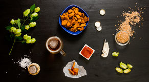 Beer set. Glass of beer, crackers, ketchup, salt. The ingredients for brewing: malt and hops. On a wooden black background. Stock Images