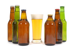 Glass of lager beer with several bottles in a row isolated on white background Stock Images