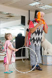 Beer-Sheva, ISRAEL -Clown inflates the balloon and girl with hoop, July 25, 2015 Stock Photos