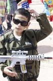 Beer-Sheva, ISRAEL - March 5, 2015: A boy in a green suit with a toy gun soldier -Purim Royalty Free Stock Photo