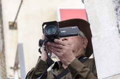 Beer-Sheva, ISRAEL - March 5, 2015: An elderly man in a hat with a video camera - Purim Royalty Free Stock Photo