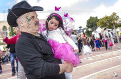 Beer-Sheva, ISRAEL - March 5, 2015:An elderly man with a mustache, with a festive make-up in black and a black cowboy hat and hold. S a little girl in a pink Royalty Free Stock Photography
