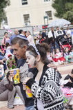 Beer-Sheva, ISRAEL - March 5, 2015: Father and daughter in costume drink juice in the crowd on the street - Purim Royalty Free Stock Photo