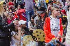 Beer-Sheva, ISRAEL - March 5, 2015: Girl dressed as police and boy in T-shirt. Fly Emirate in a crowd of children and parents on holiday Purim in the city of Royalty Free Stock Image