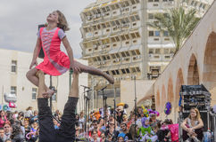 Beer-Sheva, ISRAEL - March 5, 2015:Girl and man - gymnasts perform for the audience at the open stage -Purim Stock Photo