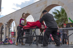 Beer-Sheva, ISRAEL - March 5, 2015: Magician performs on the street scene hypnosis session with the girl in red -Purim. In the city of Beer-Sheva on March 5 stock images