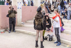Beer-Sheva, ISRAEL - March 5, 2015: The man with the video camera shoots people in carnival costumes. Girl in black with long hair Stock Photos