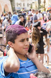 Beer-Sheva, ISRAEL - March 5, 2015:Portrait of a teenage boy in a blue T-shirt with purple red hair with a mobile phone in a crowd. Purim in the city of Beer Stock Photo