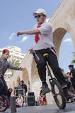 Beer-Sheva, ISRAEL - March 5, 2015:  Teenager boy on bicycle wheels, one stands on the open stage - Purim Stock Photos
