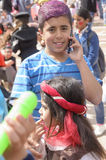Beer-Sheva, ISRAEL - March 5, 2015: Teenager boy with purple hair dyed in a blue striped shirt with mobile phone and girl sister,P Royalty Free Stock Image