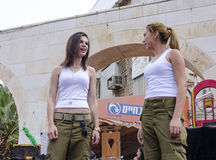 Beer-Sheva, ISRAEL - March 5, 2015: Two girls in white shirts and green pants soldiers look at each other while performing on stag. E -Purim in the city of Beer royalty free stock image