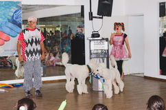 Beer-Sheva, ISRAEL -Two clowns, two white poodle and children in the audience hall, July 25, 2015 Stock Photography