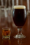 Beer and a shot. Of whiskey served on a busy out of focus bar Royalty Free Stock Photos