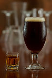 Beer and a shot. Of whiskey served on a busy out of focus bar Royalty Free Stock Image