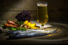 Beer with shrimp and fresh herbs. Still life with beer, shrimp, stockfish and fresh herbs Stock Photos