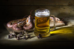 Beer with shrimp. Still-life with a glass of fresh beer and cooked shrimp Royalty Free Stock Images