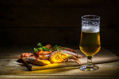 Beer with shrimp. Still life with beer, shrimp and herbs Stock Image