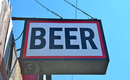 Beer Sign. A sign for beer hangs outside of a bar with a blue sky in background royalty free stock photos