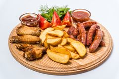 Beer snack set with tomato sauce, adzhika on a wooden board. White background royalty free stock image