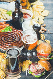 Beer and snack set on dark wooden scorched background. Beer and snack set. Octoberfest food frame concept. Variety of beers, grilled sausages, burgers, fried Royalty Free Stock Images