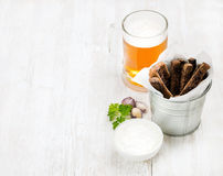 Beer snack set. Pint of pilsener in glass mug and rye bread croutons with garlic cream cheese sauce over white painted Royalty Free Stock Image
