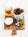 Beer snack set. Pint of pilsener in mug, open glass bottle, rye bread croutons with garlic cream cheese sauce and fresh Stock Photos