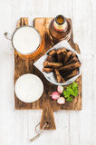 Beer snack set. Pint of pilsener in mug, open glass  bottle, rye bread croutons with garlic cream cheese sauce on rustic Royalty Free Stock Images