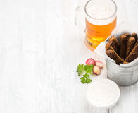 Beer snack set. Pint of pilsener in mug and rye bread croutons with garlic cream cheese sauce over white painted old Stock Photography