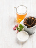 Beer snack set. Pint of pilsener in tall mug and rye bread croutons with garlic cream cheese sauce over white painted Royalty Free Stock Image