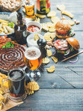 Beer and snack variety on dark wooden scorched background. Beer and snack set. Octoberfest food frame concept. Beers assortment, grilled sausages, burgers, fried Royalty Free Stock Photography