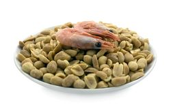 Beer snacks. Boiled shrimps and salted peanuts on the plate. Snacks for beer Stock Image