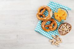 Beer snacks. On wooden table. Nuts, chips, pretzel. Top view with copy space royalty free stock images